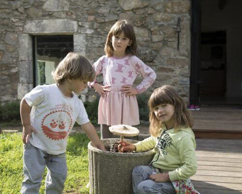 three small children sitting and playing with a mushroom in nature one child is using medical cannabis for seizures