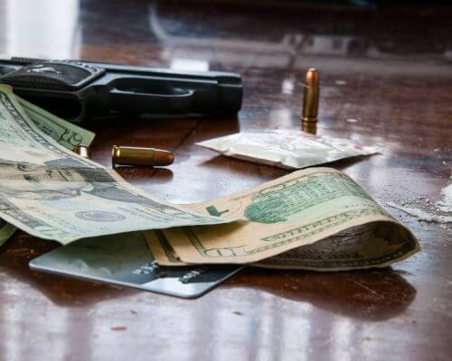 money, gun, bullet on table representing the difficulties ahead of the philipines war on drugs while legal medical marijuana is accessible