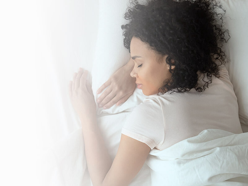Woman sleeping in her bed with piece of mind
