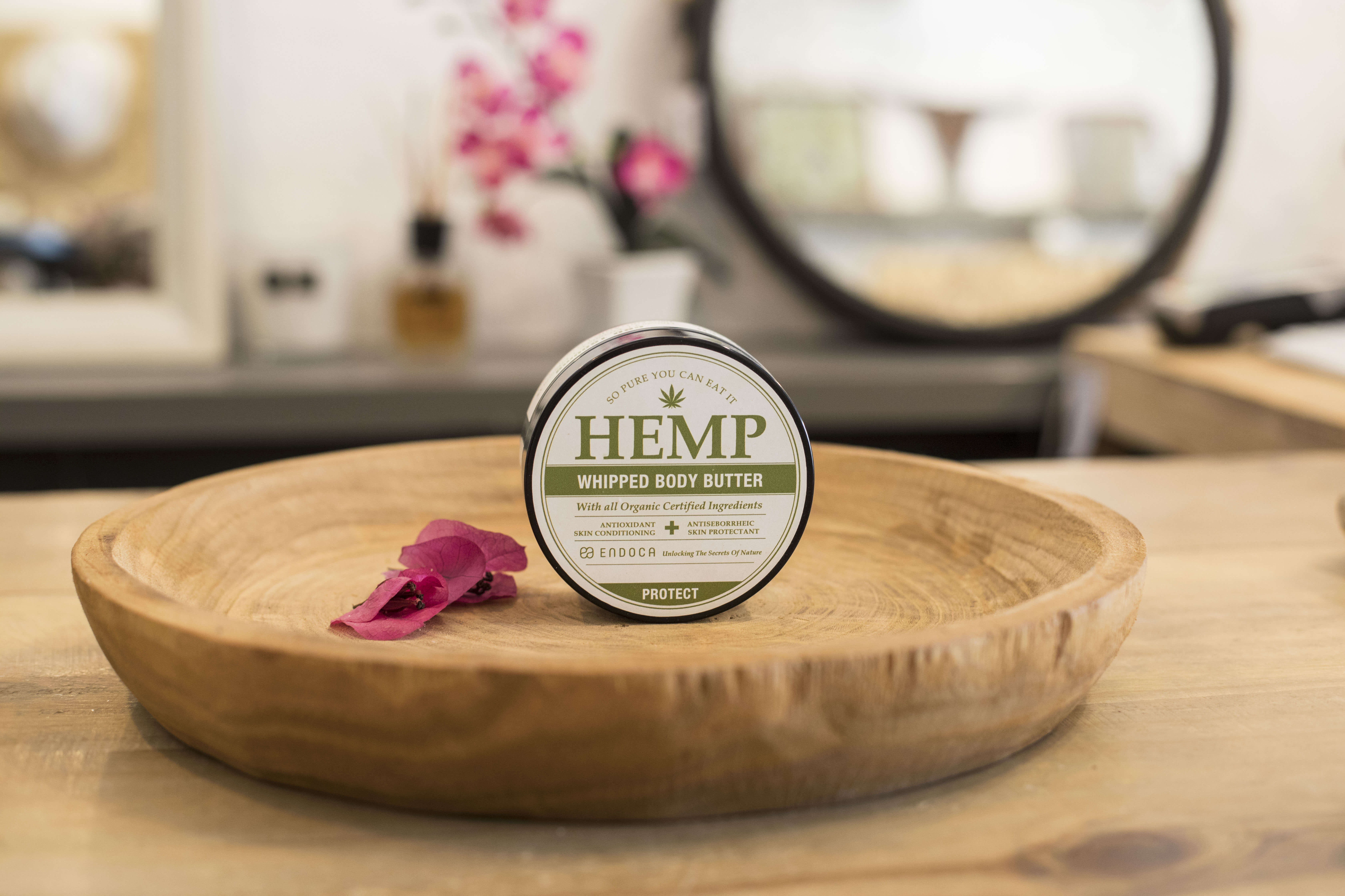 CBD body butter medical cannabis product sits on kitchen bench next to petal