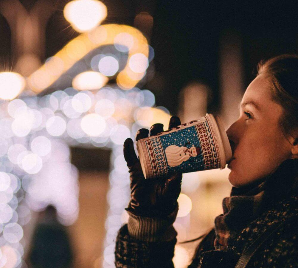 woman drinking coffee near Christmas lights