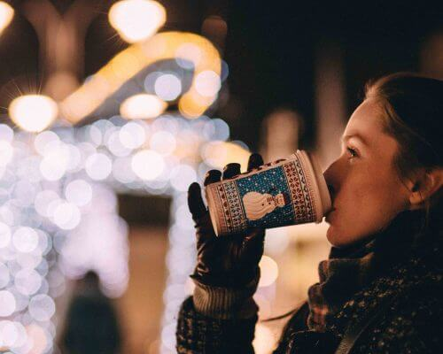woman drinking coffee near Christmas lights