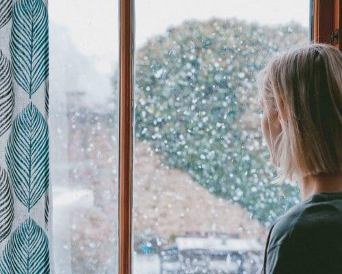 Woman drinking tea near a window with snow
