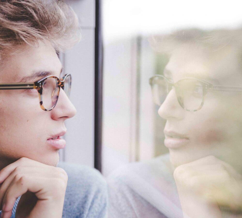Young man thinking and looking out the window
