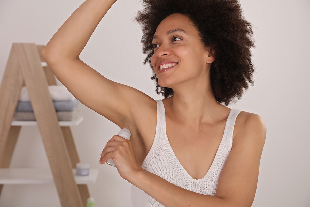 CBD deodorant-woman putting on deodorant.