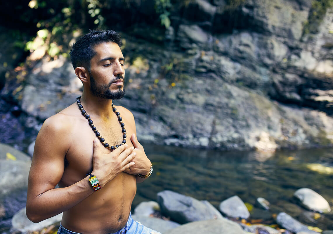 man with beard sitting with hands over his chest meditating