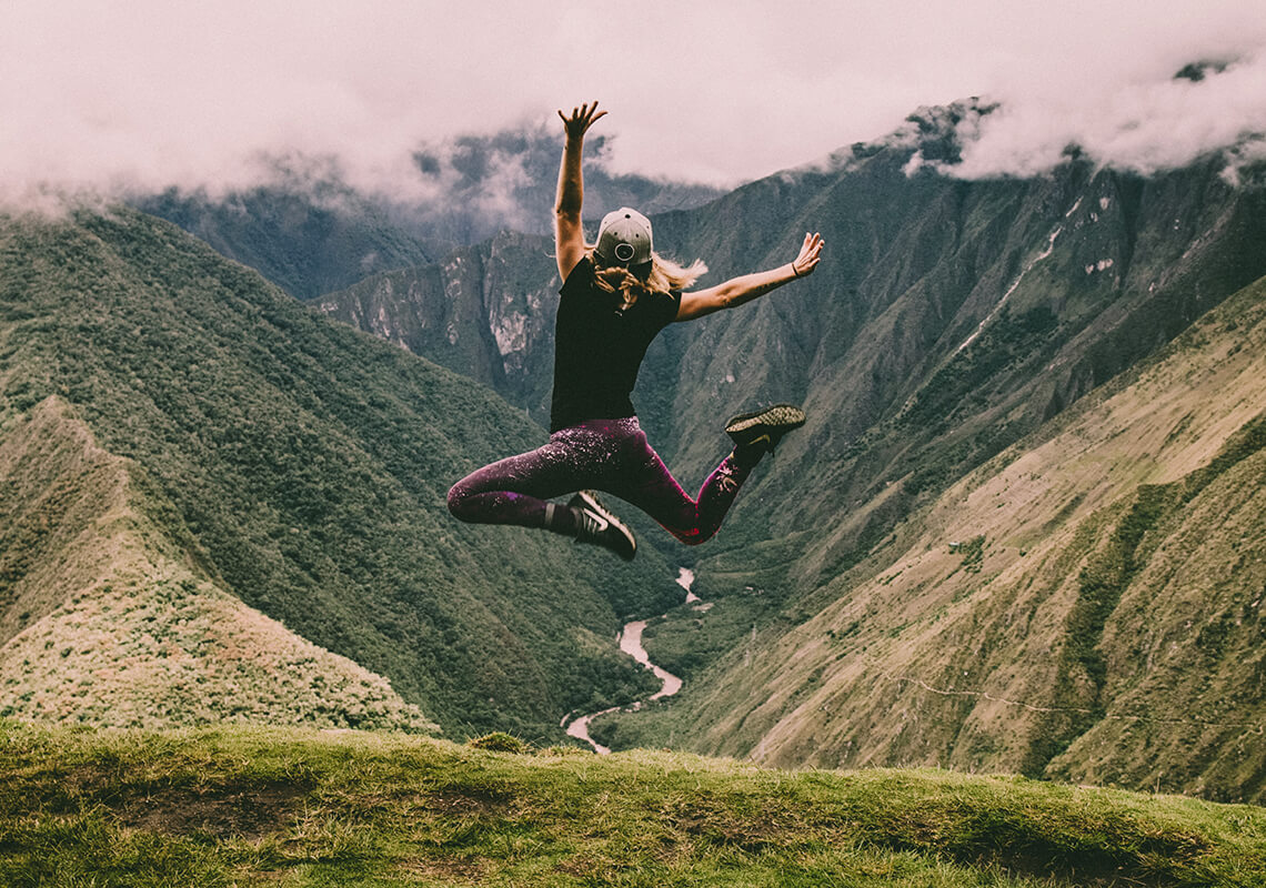 Girl jumping in air overlooking mountains