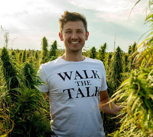 Man in hemp field wearing white t-shirt with words 'walk the talk'