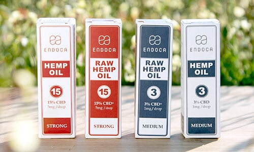 Four CBD oils in paper packing lined up in front of green background