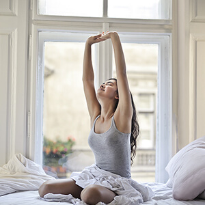 woman in grey shirt stretching after sleeping