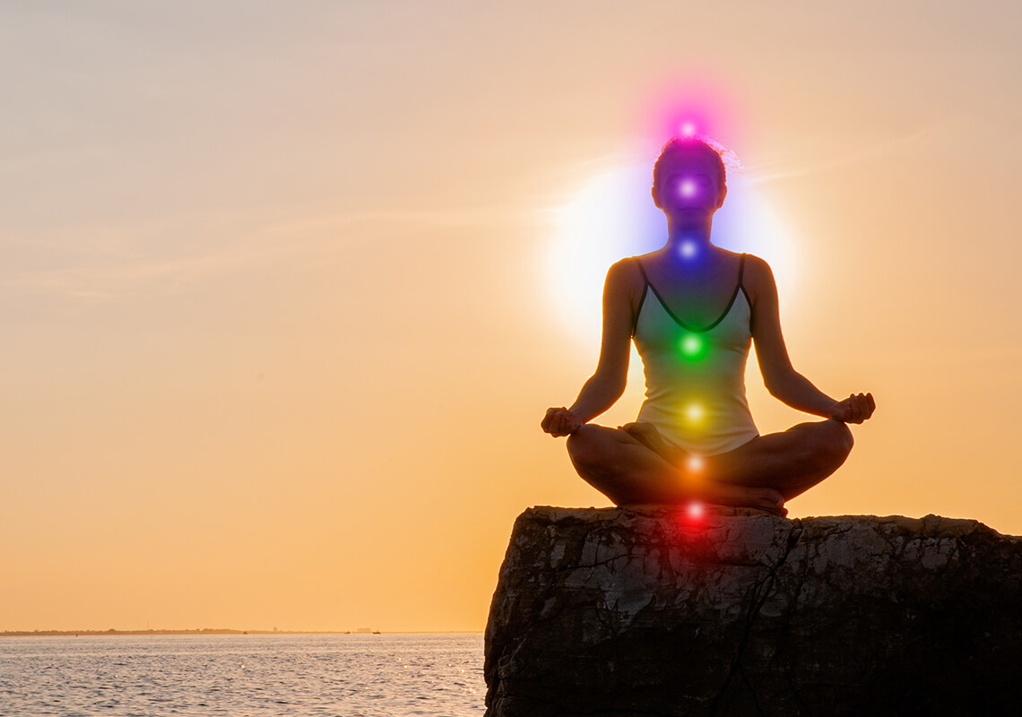 woman meditating on rock with chakras aligned