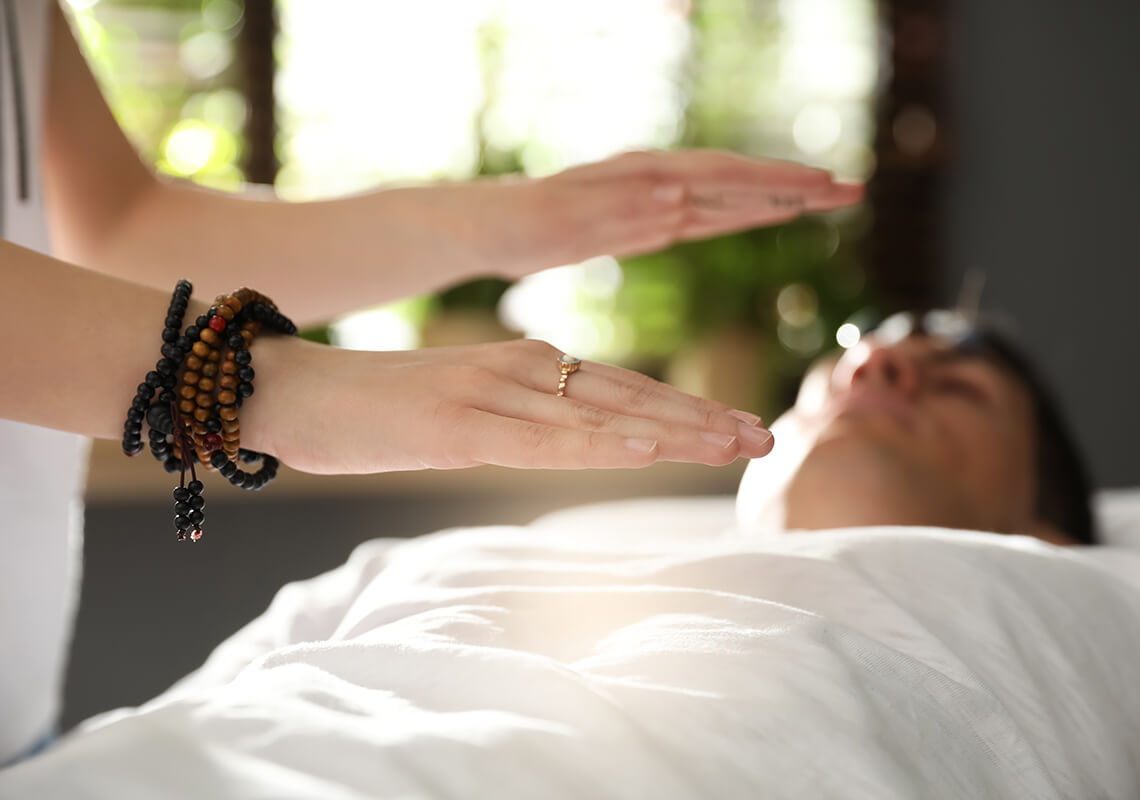 hands performing reiki above a person wearing a white shirt