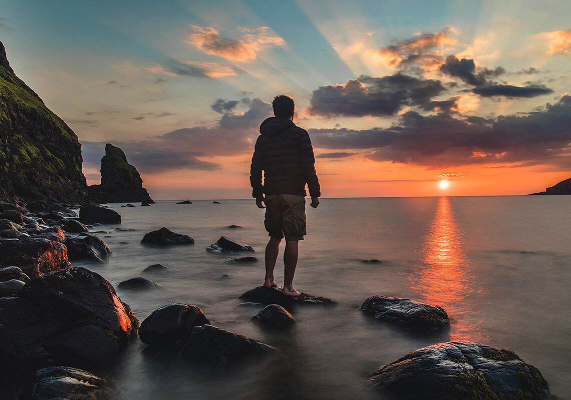 man standing on rock looking over water at sunset